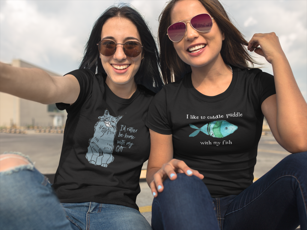 Two women wearing I'd rather be home with my cat, I want to cuddle puddle with my fish t-shirts